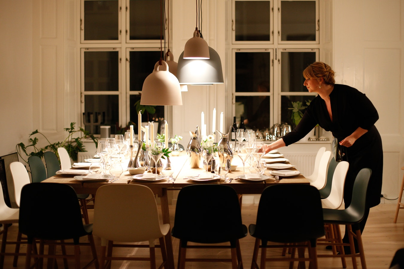 Woman setting a large dinner table for Christmas Eve dinner
