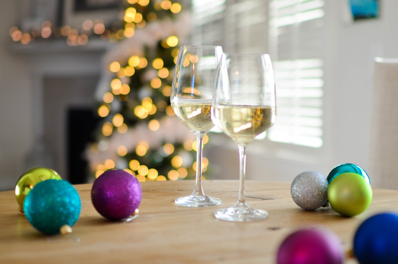 Ornaments and Wine on a table in front of a Christmas Tree