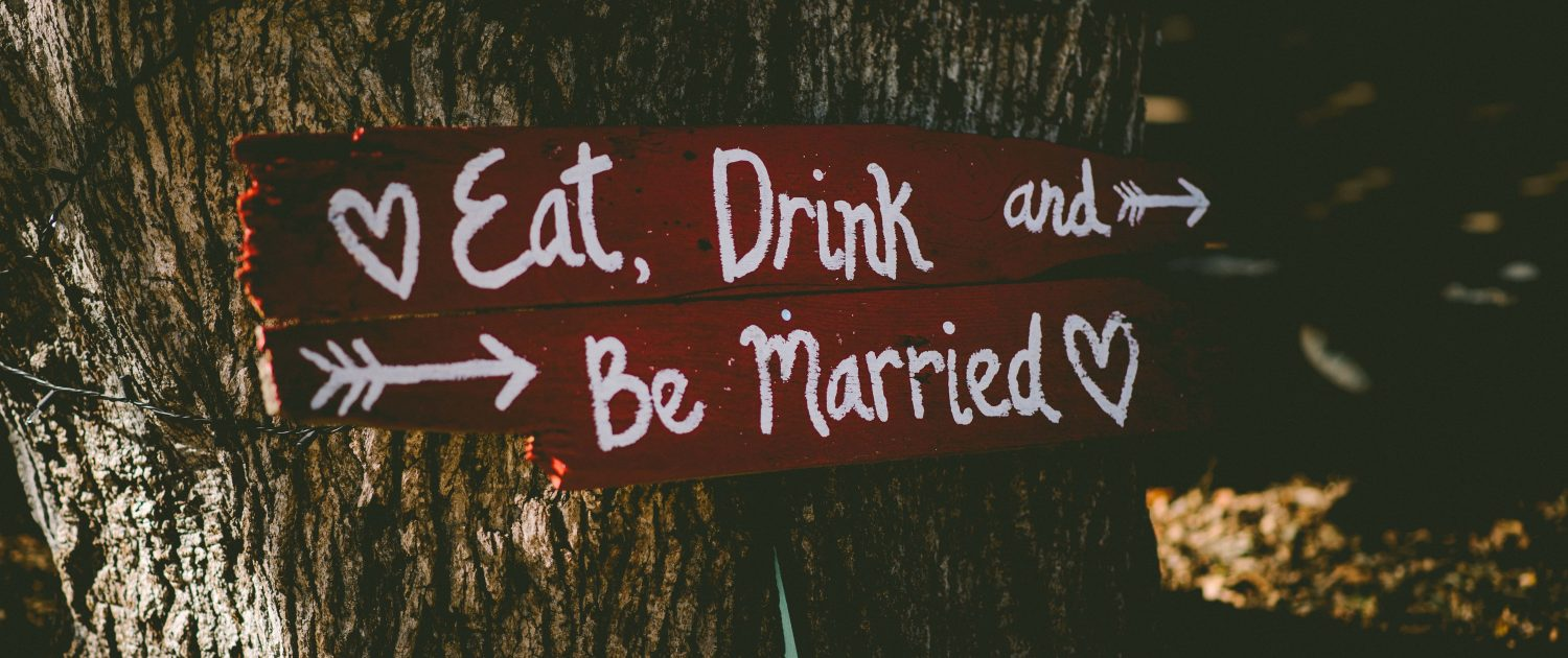 """Wooden sign on a tree with the following message carved into it: """"Eat, Drink, and Be Married"""""""