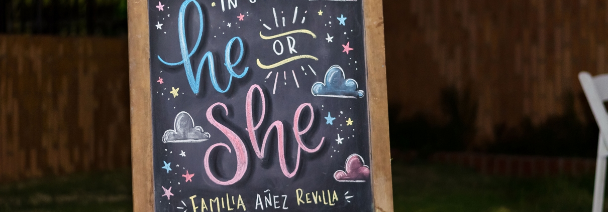 """A colorful Gender Reveal Sign that reads """"Baby coming in July: He or She?"""""""
