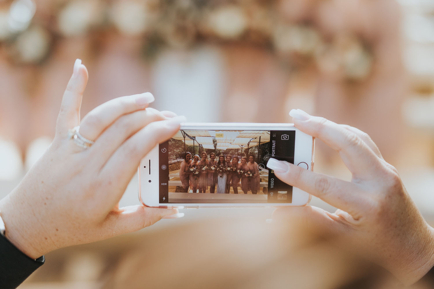 A woman's hands hold a cell phone and take a photo of a wedding