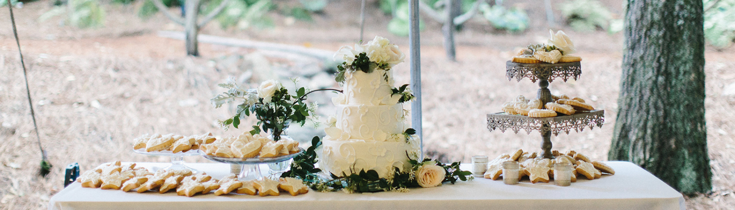 A beautiful wedding dessert display including a elegant white wedding cake and white cookies